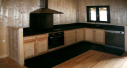 L'ensemble des murs de la maison est habillé en sapin. Création des meubles de cuisine dans « le même esprit  bois »