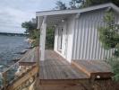 Cabane de jardin en bois habillée de volige couvre-joint teintée en blanc. Terrasse en ipé et escalier d'accés à la plage.