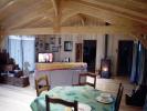 Autre exemple de salon/salle à manger de 6 m de largeur, habillée de lambris en peuplier. Le sol est en pin maritime vitrifié. Chauffage par un poêle à granulés.